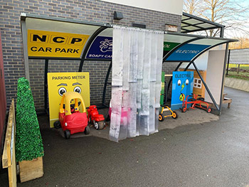 Bike shed transformed into a car park and fuel station at a nursery school with signage and graphics