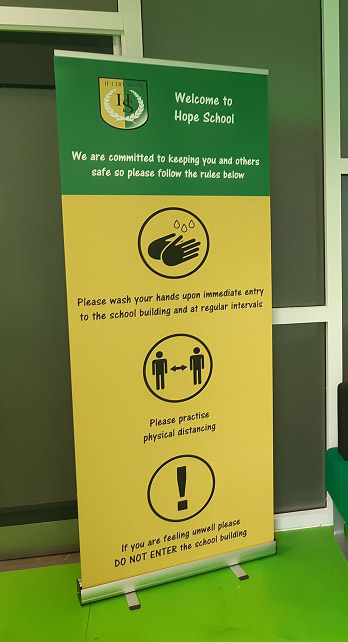 Banner stand for a Primary School displaying Coronavirus Covid 19 social distancing and hygiene message