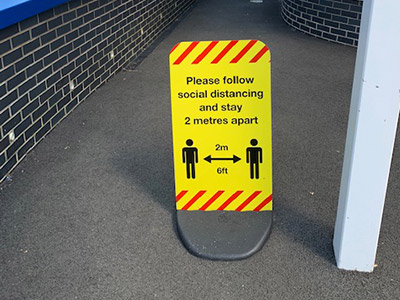 Pavement sign with Covid-19 social distancing message for schools