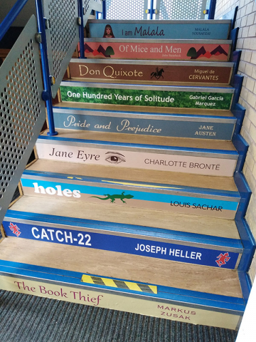 Book spine stair graphics on the risers of steps in a school
