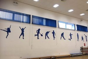 Silhouette signage on a school sports hall wall